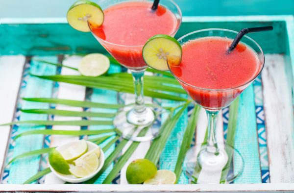 Strawberry margarita cocktail on colorful wooden background with palm leaf